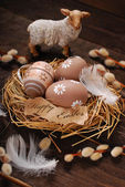 Easter eggs and paper tag with greetings in nest — Stock Photo