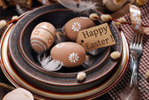 Easter eggs and paper tag with greetings in plate on rustic tabl — Stock Photo