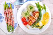Dinner with green asparagus baked on eggs — Stock Photo