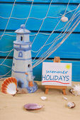 Seaside summer holidays still life with text written on easel — Stock Photo