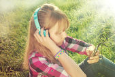 Girl listening music on the meadow in vintage style  — Stock Photo