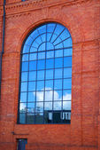 Reflection of of blue sky in window of old factory in Lodz — Stock Photo