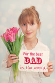 Girl with flowers and greetings  for dad — Stock Photo