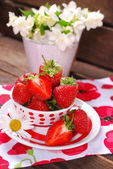 Bowl of fresh strawberries on wooden table — Stock Photo