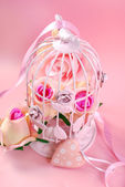Roses in pink metal cage — Stock Photo