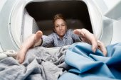 Woman reaching in a dryer for clothes — Stock Photo