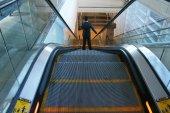 Man riding down an escalator — Stock Photo