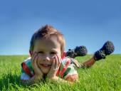Boy laying in the grass — Foto de Stock