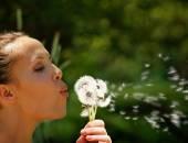 Woman blowing on dandelion — Stock Photo