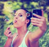 Pretty girl blowing bubbles — Stock Photo