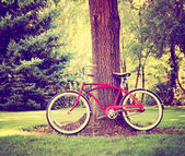 Old bike leaning against tree — Stock Photo