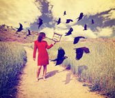 Girl in field with birds — Stock Photo