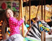 Girl riding on a merry go round — Stock Photo
