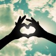 Two hands making heart shape in sky — Stock Photo #53620781