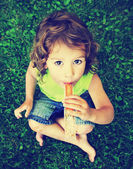Girl eating frozen treat in grass — Stockfoto