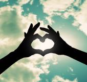 Two hands making heart shape in sky — Stock Photo