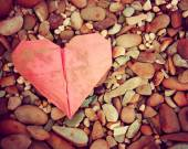 Discarded paper heart on rocks — Stock Photo