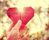 Hand holding an origami paper heart up — Stock Photo