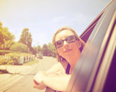 Woman with head out of car — Stock Photo