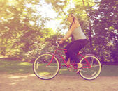 Girl riding a bike in a park — Stock Photo