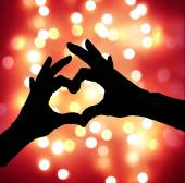 Defocused lights with heart hands silhouette — Stock Photo