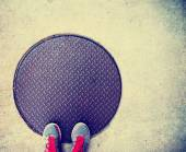 Feet on a manhole cover — ストック写真