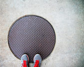 Feet on a manhole cover — Stock fotografie