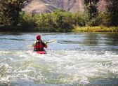 Woman kayaking on rough river — Stock Photo