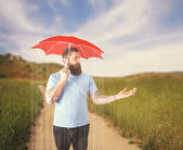 Guy in thunderstorm under umbrella — Stock Photo