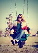 Pretty woman sitting in swing — Stock Photo