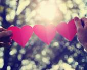 Hands holding string of paper hearts — Stockfoto