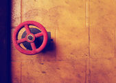 Red water valve on yellow wall — Foto Stock