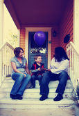 Cute family sitting on porch — Stock Photo