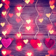 Felt fabric love valentine's hearts hanging on rustic driftwood — Stock Photo #62011601