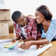 African couple deciding on paint colour — Stock Photo #74603367