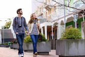 Couple walking with camera in city — Stock Photo