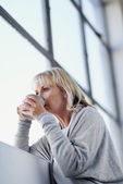 Blonde woman sipping a cup of tea — Stock Photo