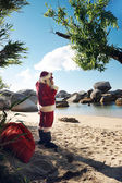 Santa Claus standing on a beach — Stock Photo