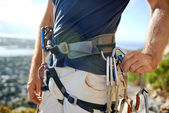 Man in harness and rockclimbing equipment — Stock Photo