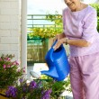 Retired woman watering her plants — Stock Photo #74975223
