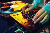 Dj hands on equipment deck and mixer — Stock Photo