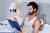 Man on bed reading book — Stock Photo