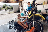 Boy helping dad with fixing motorcycle — Stock Photo