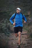 Runner training in mountains — Stock Photo