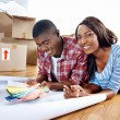 African couple deciding on colour swatch — Stock Photo #74984859
