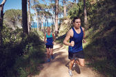 Couple trail running together — Stockfoto