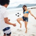 Latino couple playing soccer on beach — Stock Photo #74994879