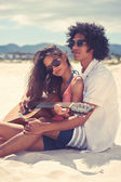 Hispanic couple playing guitar on beach — Stock Photo