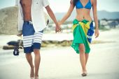 Couple walking with surfboard and flag as sarong — Stock Photo