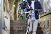 Man carrying bicyle down stairs in city — Stock Photo